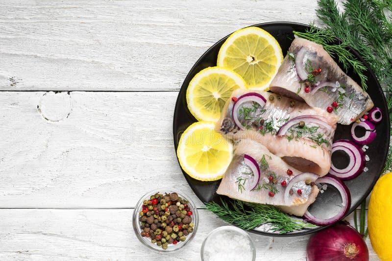 Prendedero de arenques con la sal, la pimienta, las hierbas, la cebolla y el limón en la placa negra con los ingredientes foto de archivo libre de regalías