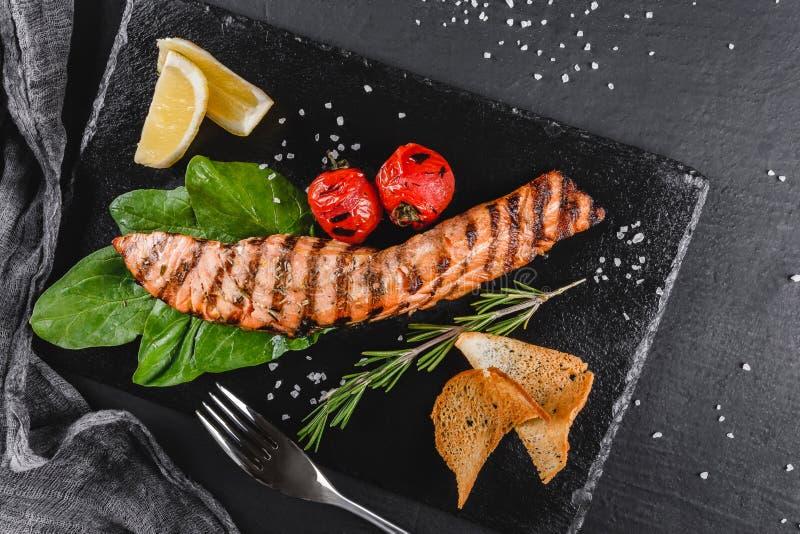 Prendedero de color salmón asado a la parrilla adornado con la espinaca, limón, hierbas en la placa sobre fondo de madera Plato d imagen de archivo libre de regalías