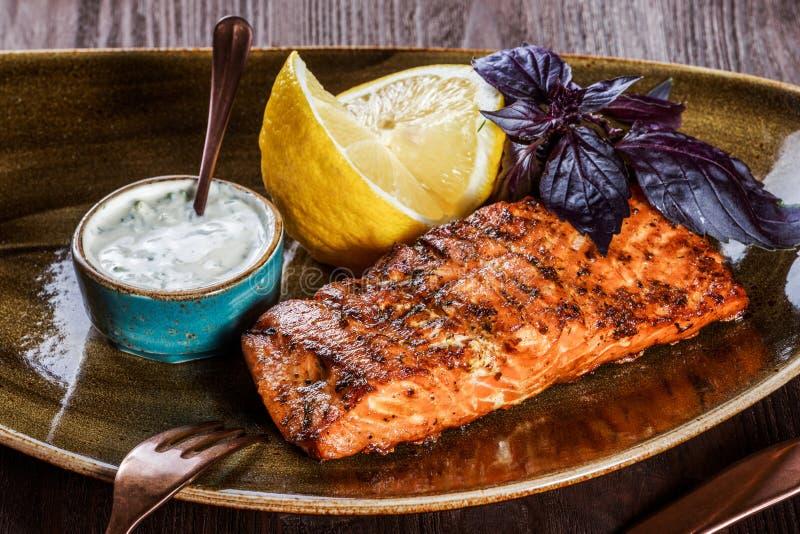 Prendedero de color salmón cocido con la salsa, la albahaca y el limón de queso en la placa en fondo de madera fotos de archivo