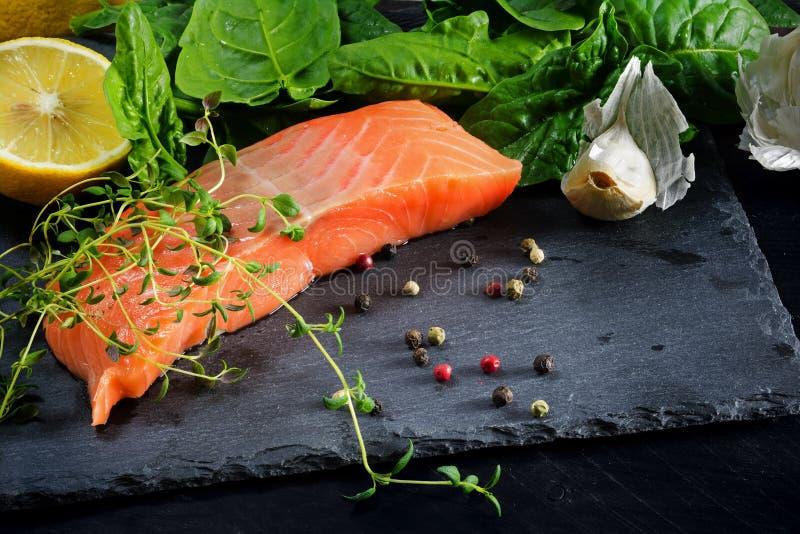 Prendedero de color salmón crudo con tomillo, ajo, el limón y las especias en una oscuridad imagen de archivo libre de regalías