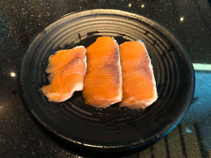 Prendedero de color salmón crudo en plato negro en restaurante imagen de archivo