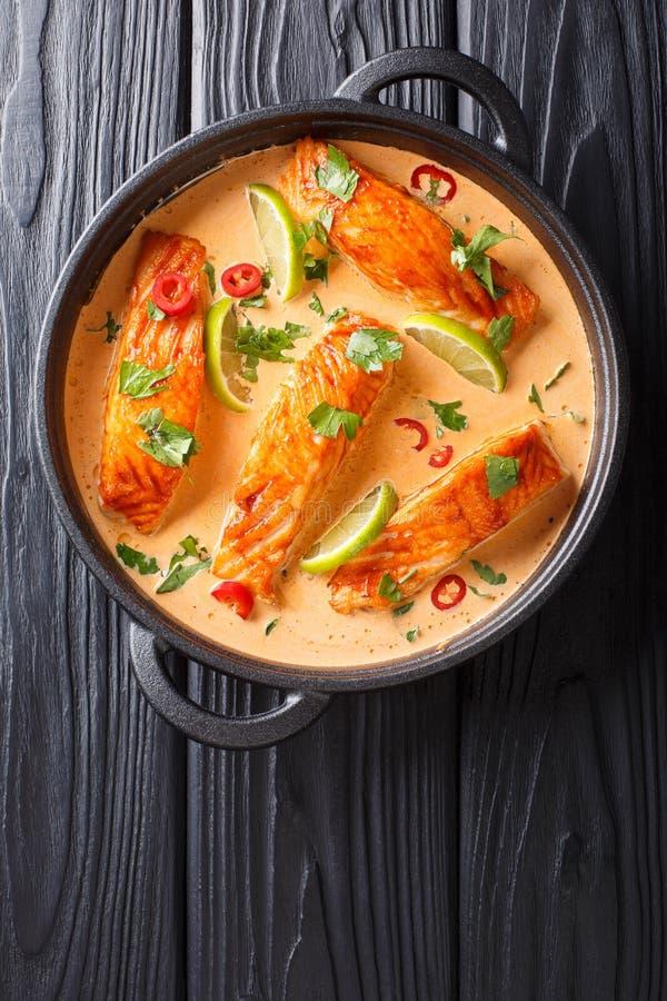Prendedero de color salm?n blando en curry tailand?s picante del coco con la cal y el primer de las hierbas en una cacerola Visi? fotos de archivo
