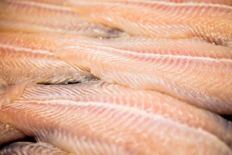 Prendedero de los pescados Pangasius en la placa negra del hielo para cocinar en mercado fresco fotografía de archivo