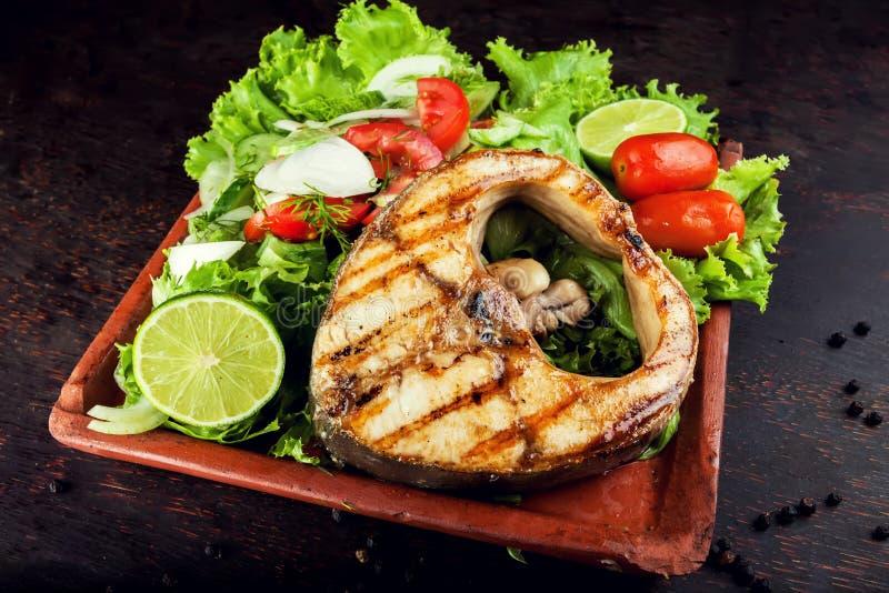 Prendedero de pescados asado a la parrilla con las verduras en la placa fotos de archivo