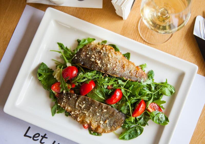 Prendedero de pescados chamuscado delicioso con el vino en fondo del restaurante fotos de archivo