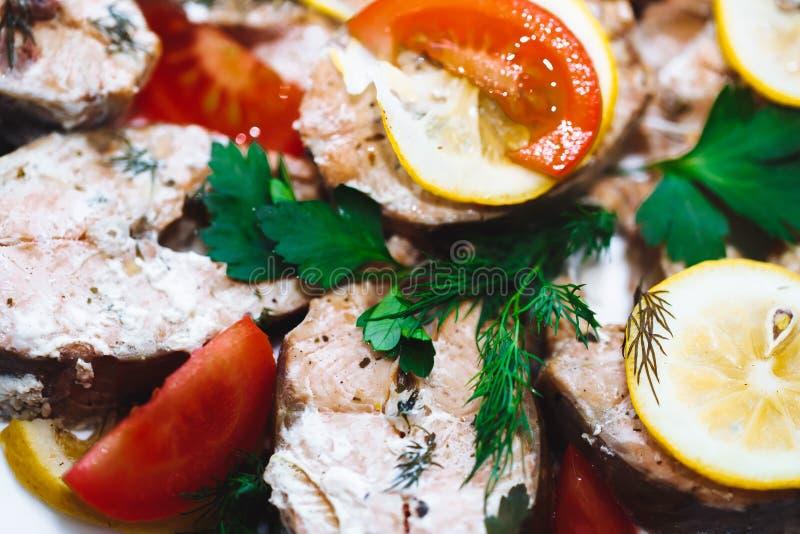 Prendedero de pescados de color salmón cocido con los tomates, especias , limón Menú de la dieta Comida sana, mariscos, verduras, fotografía de archivo libre de regalías