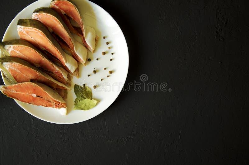 Prendedero de pescados de color salm?n crudo en fondo negro fotografía de archivo