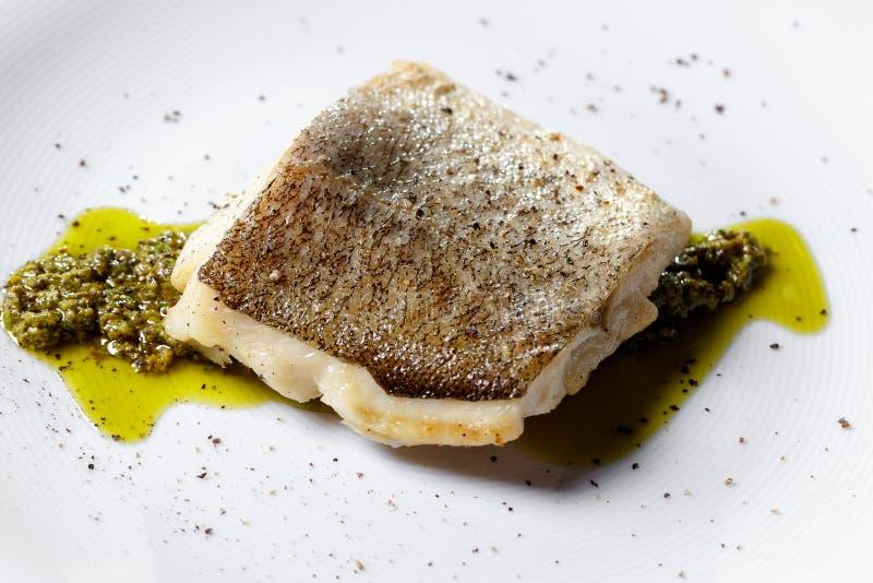 Prendedero de pescados frito, bacalao atlántico con romero en la placa blanca fotografía de archivo libre de regalías