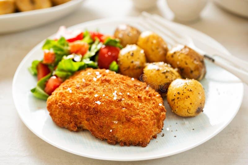 Prendedero empanado tradicional del bacalao con las patatas y la ensalada del bebé fotos de archivo libres de regalías