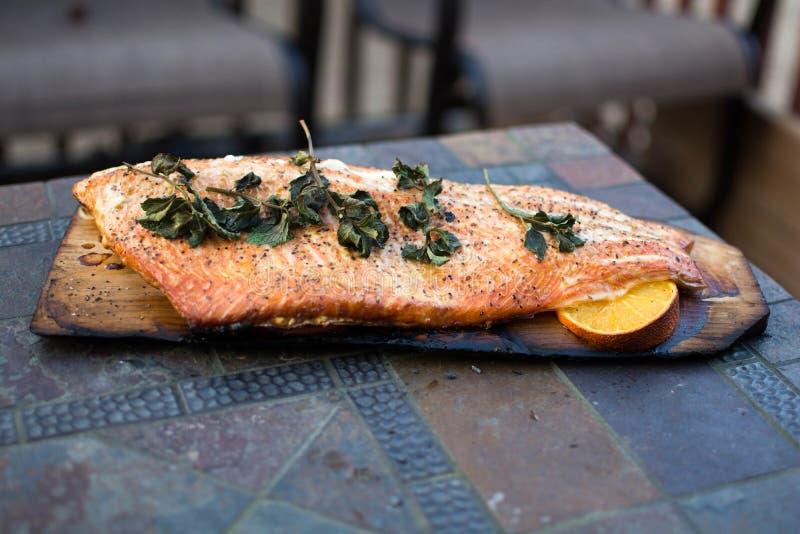 Prendedero entero de color salmón asado a la parrilla hecho en casa en Cedar Plank foto de archivo libre de regalías