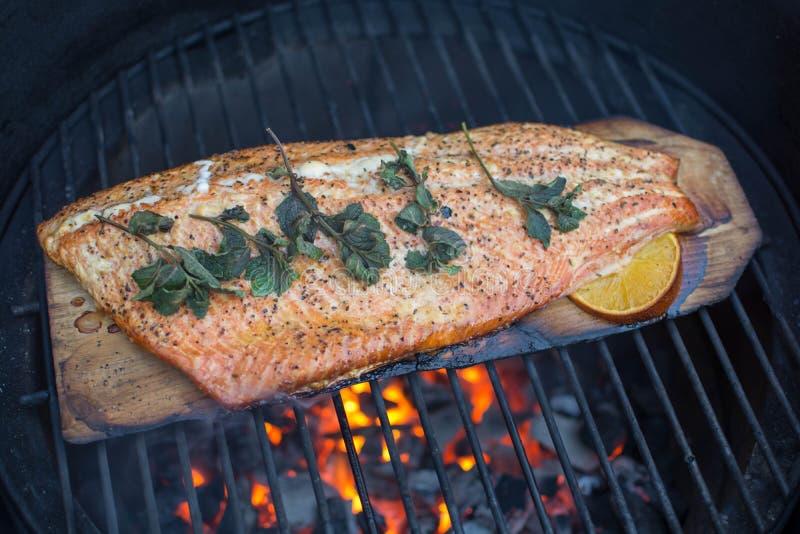 Prendedero entero de color salmón asado a la parrilla hecho en casa en Cedar Plank fotos de archivo libres de regalías