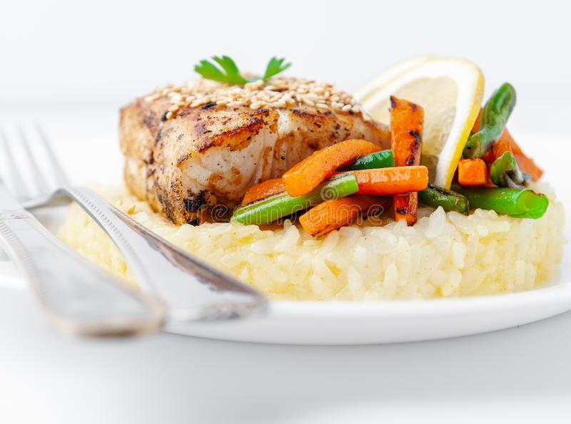 Prendedero frito de la perca con arroz y verduras En una placa blanca con los cubiertos En un fondo blanco Primer aislado imagen de archivo libre de regalías