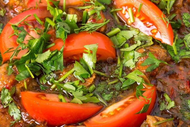 Prendedero guisado delicioso del cerdo con los tomates frescos fotografía de archivo