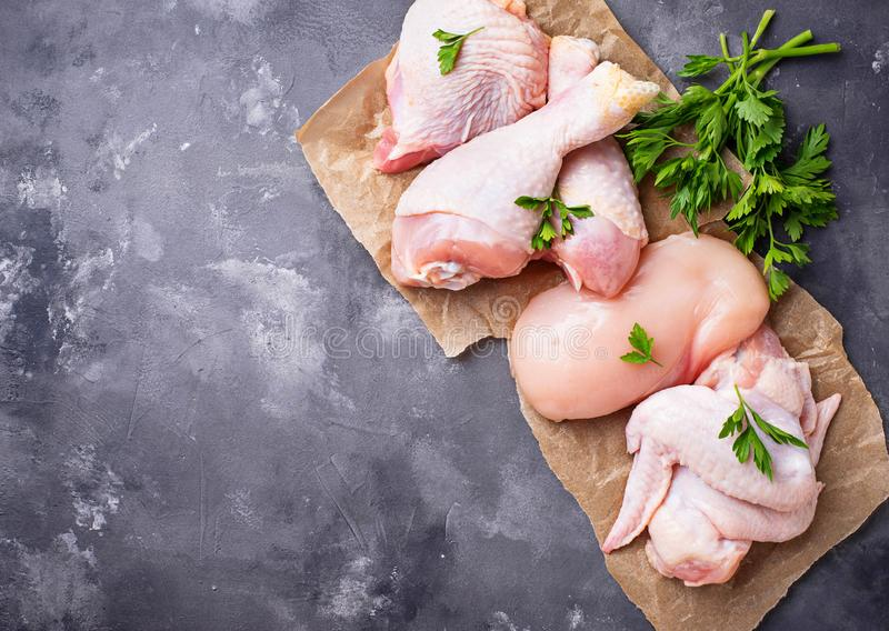 Prendedero, muslo, alas y piernas crudos de la carne del pollo imagenes de archivo