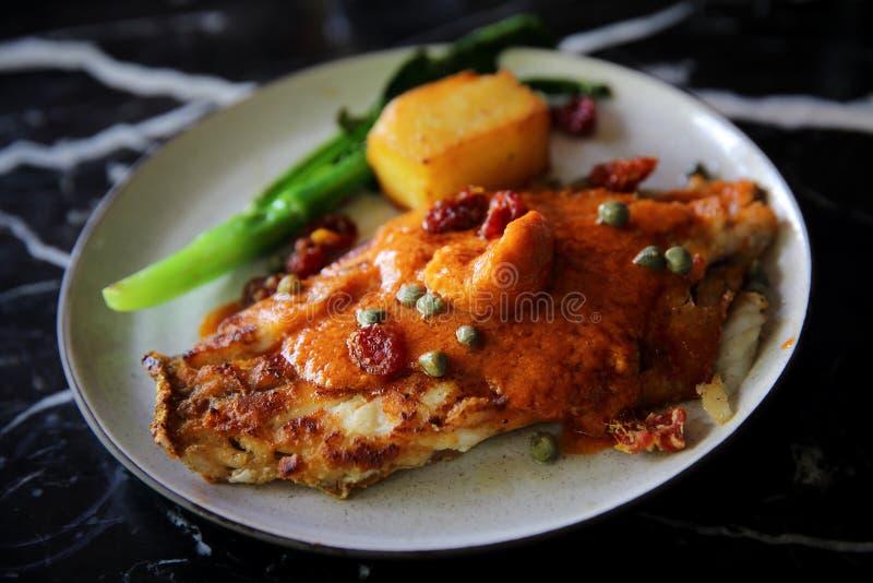 Prendederos de cena finos de la lubina con el tomate y la salsa de las especias fotos de archivo
