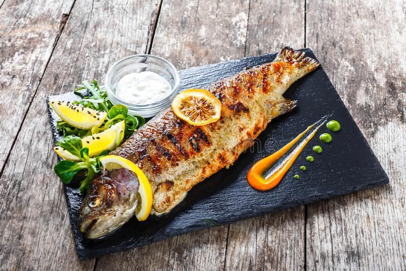 Prendederos de color salmón cocidos con el caviar y el limón rojos en el cierre de piedra del fondo de la pizarra para arriba fotos de archivo libres de regalías