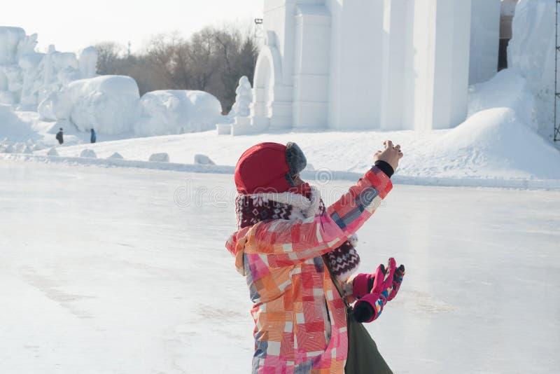 Prendendo i selfies - mano tesa della donna che prende foto al freddo di congelamento di festival della neve di Harbin fotografia stock libera da diritti