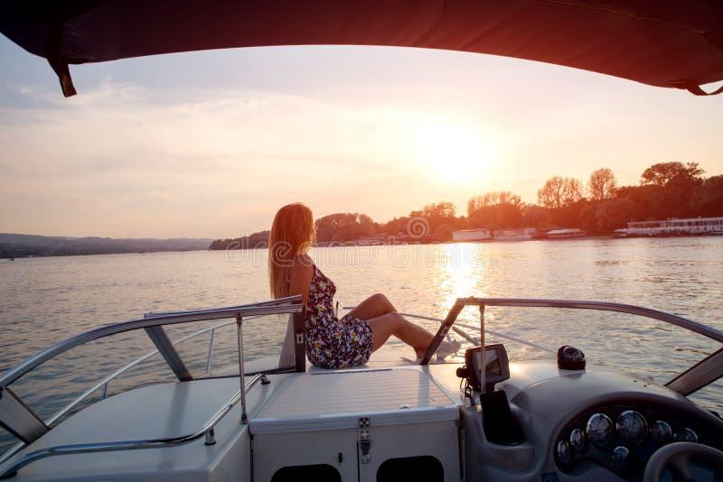 Prendendo il sole su un tramonto, sulla piattaforma anteriore di una barca immagini stock
