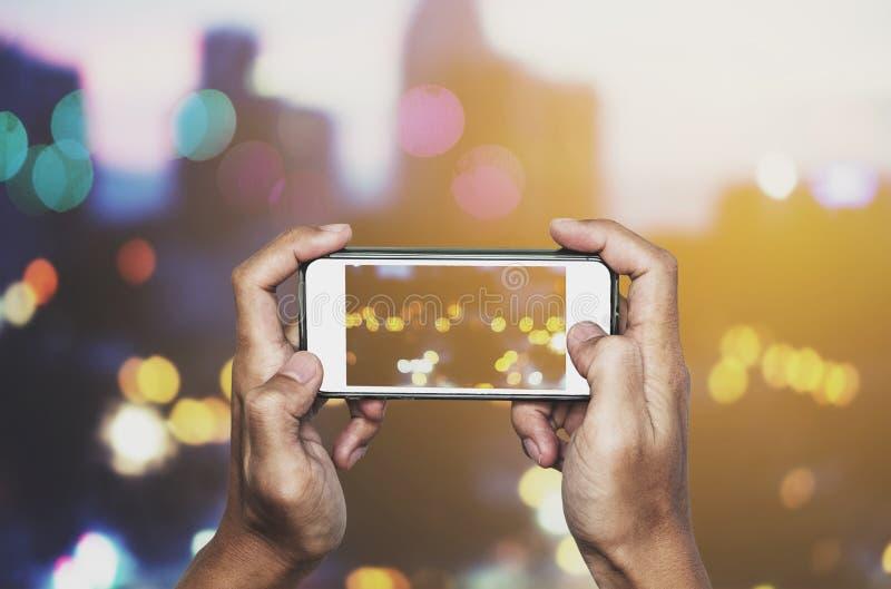 Prendendo la foto dallo Smart Phone, le mani che tengono lo smartphone che prende Bokeh si accende immagine stock