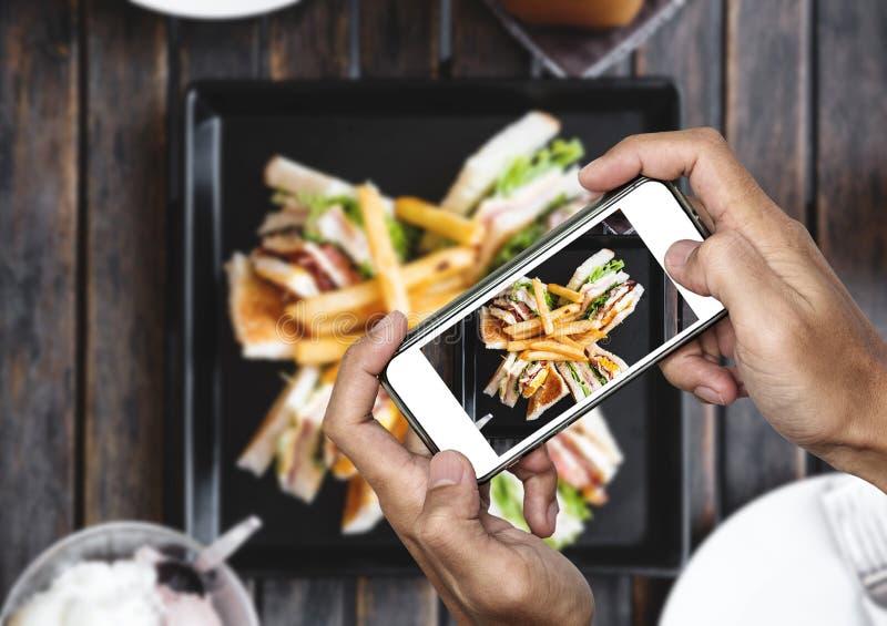 Prendendo la foto dell'alimento, fotografia dell'alimento dallo Smart Phone, panino di club con le patate fritte sulla tavola di  immagine stock