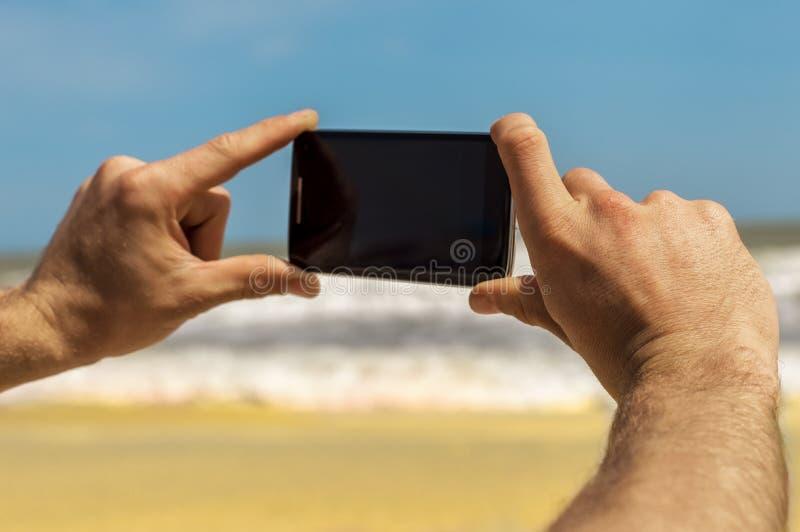 Prendendo le foto sul telefono al mare fotografia stock libera da diritti