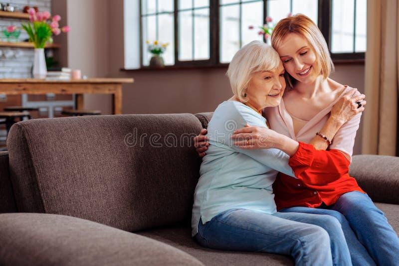 Prendendo a mulher aposentada que abraça firmemente a neta venha visitá-la foto de stock royalty free