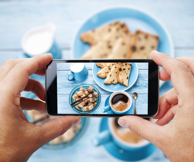 Prendendo una foto di un ` s faccia colazione con la tazza di coffe dallo smartphone fotografia stock libera da diritti