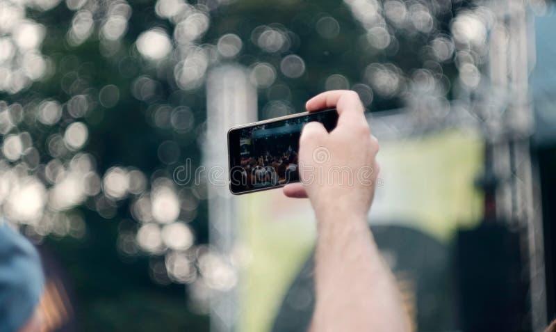 Prendre des photos avec le téléphone au concert image libre de droits