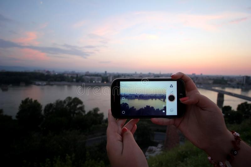 Prendre des photos de panorama du ` s de ville sur un smartphone Saunset à Novi Sad photographie stock libre de droits