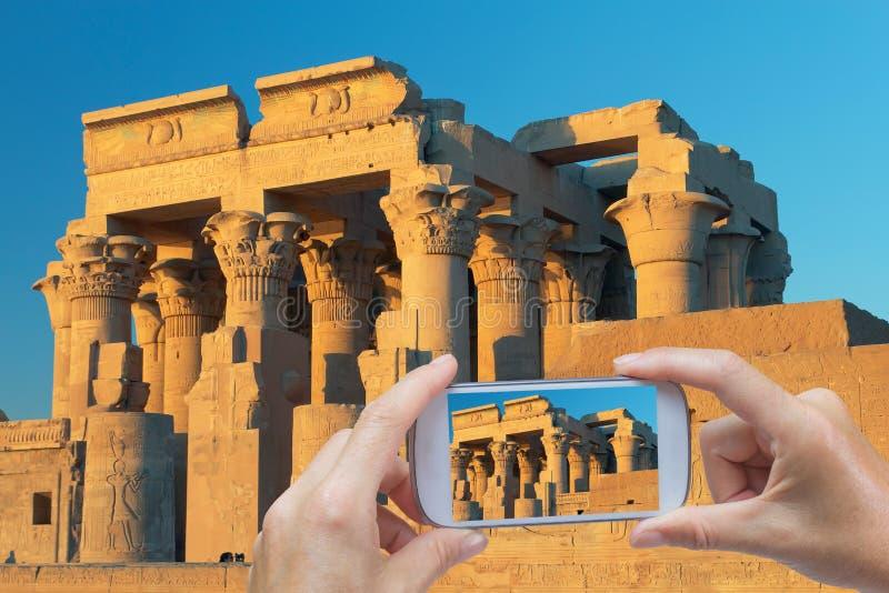 Prendre des photos par le téléphone intelligent dans le temple de Kom Ombo image stock