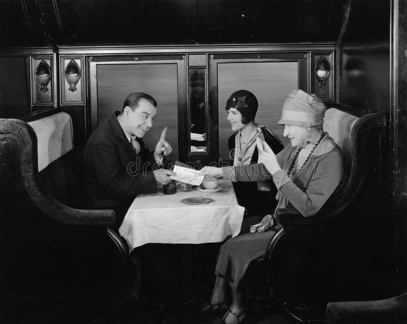 Prendre l'étiquette dans la voiture dinante de train (toutes les personnes représentées ne sont pas plus long vivantes et aucun d photographie stock libre de droits