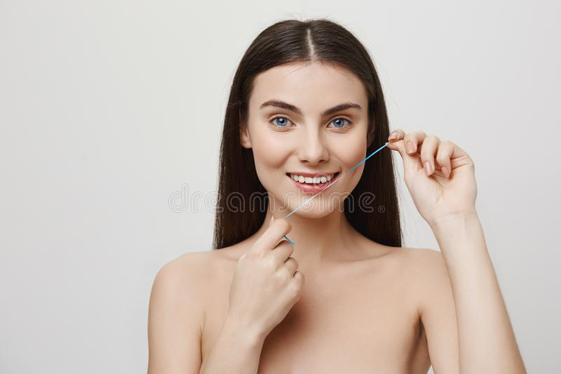 Prendre soin de sourire parfait Le studio a tiré de la belle femme obtenant le traitement pour des dents avec le fil dentaire, so photos libres de droits