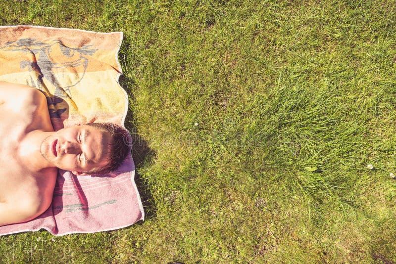 Prendre un bain de soleil de jeune homme image libre de droits