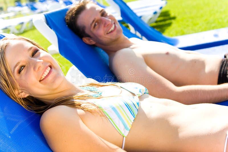Prendre un bain de soleil de jeunes couples photographie stock libre de droits