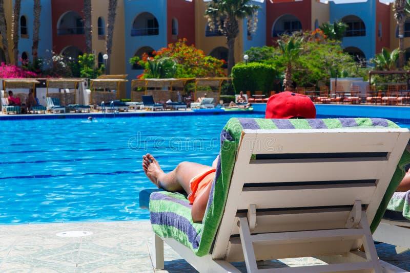 Prendre un bain de soleil par la piscine de station touristique d'hôtel photo stock