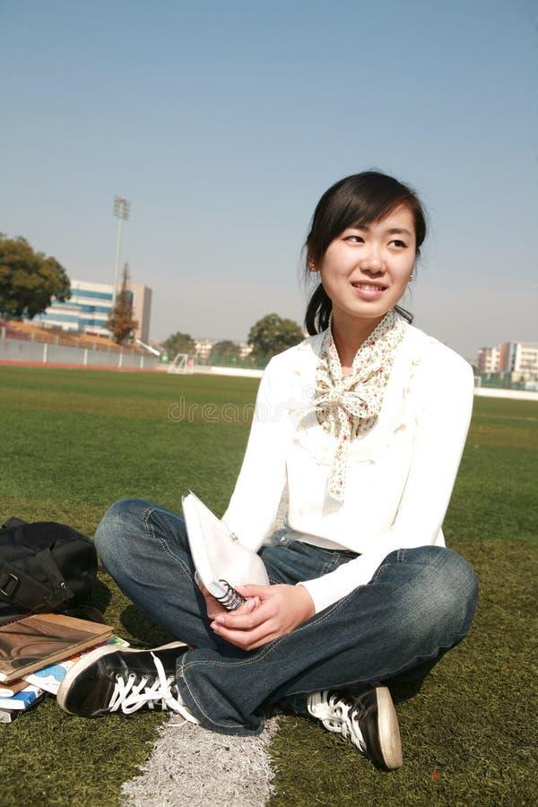prenota la seduta grasslan della holding della ragazza fotografia stock libera da diritti