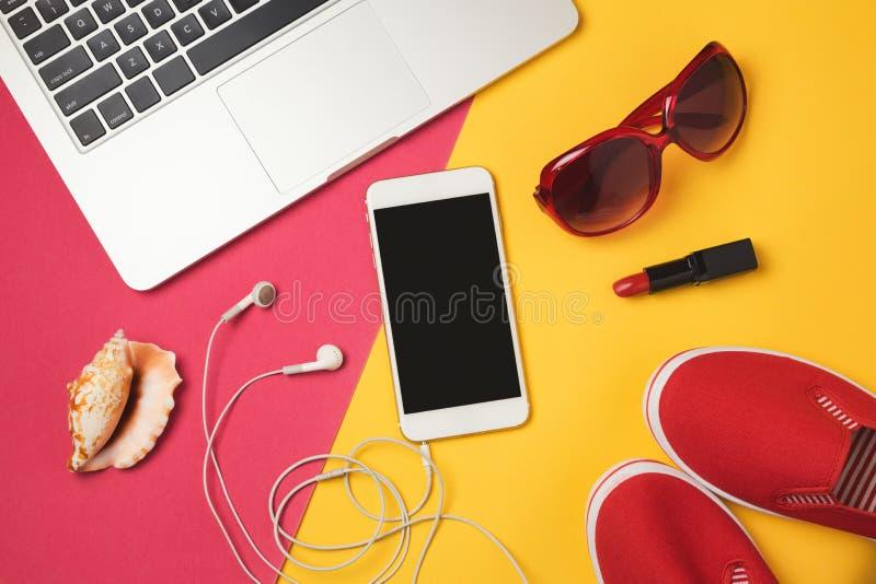 Prenotazione online per il concetto di festa di vacanze estive Oggetti di Smartphone, del computer portatile e della spiaggia Vis fotografie stock libere da diritti