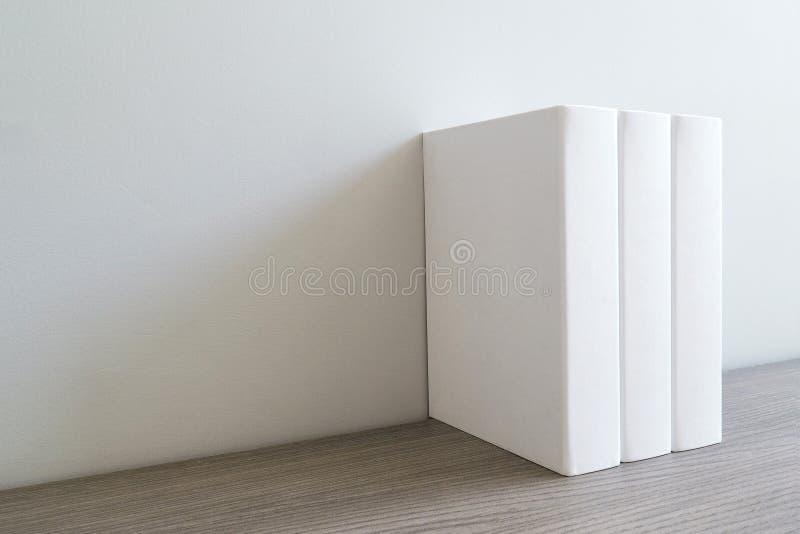 Prenoti con la copertura in bianco vuota sullo scaffale per libri bianco fotografie stock
