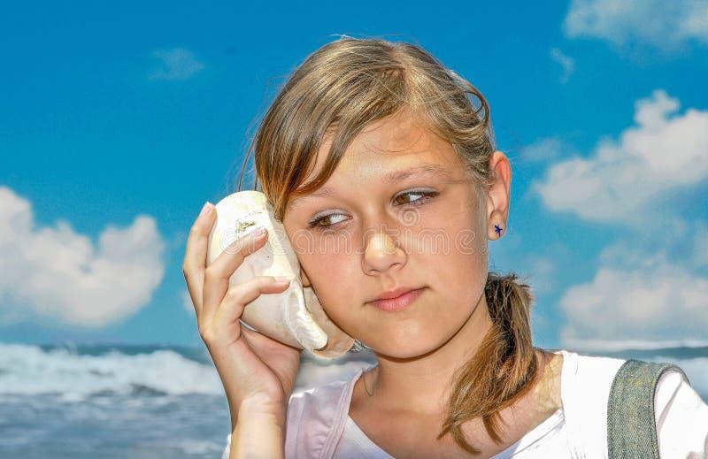 Prensa de la muchacha a su oído y a escuchar los sonidos de la cáscara fotografía de archivo