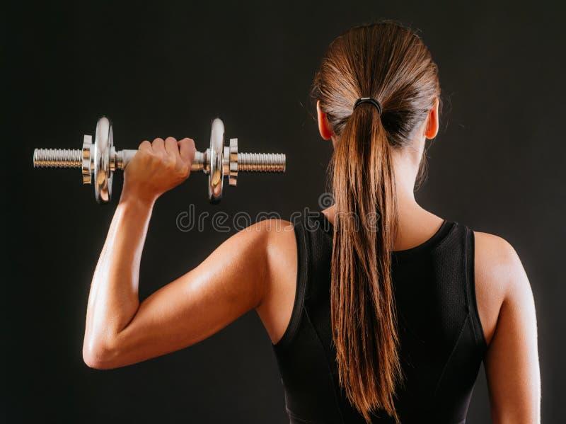 Prensa femenina del hombro que hace con pesa de gimnasia fotografía de archivo libre de regalías