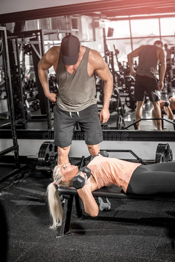 Prensa femenina del pecho de la pesa de gimnasia con ayuda del instructor personal fotografía de archivo