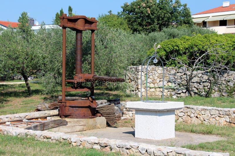 Prensa retra aherrumbrada grande del aceite de oliva del vintage del metal montada en máquina en la fundación concreta al lado de fotos de archivo libres de regalías