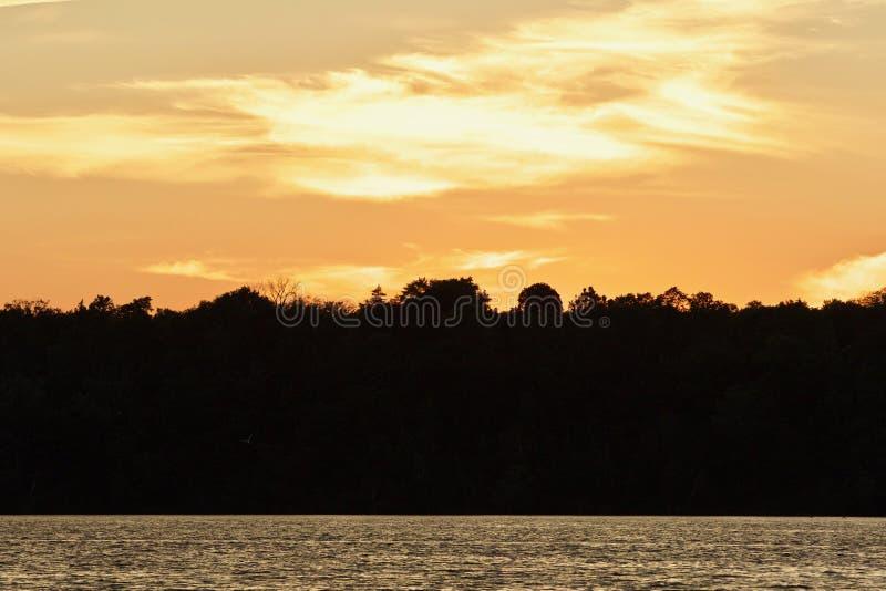 Prentbriefkaar met een verbazende zonsondergang op een meer stock foto