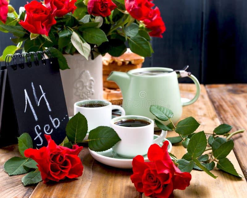 Prentbriefkaar voor de rode rozen van Valentine de Dag en Thee en bloemen voor een Romaanse ontbijt Houten achtergrond en een ket stock afbeelding