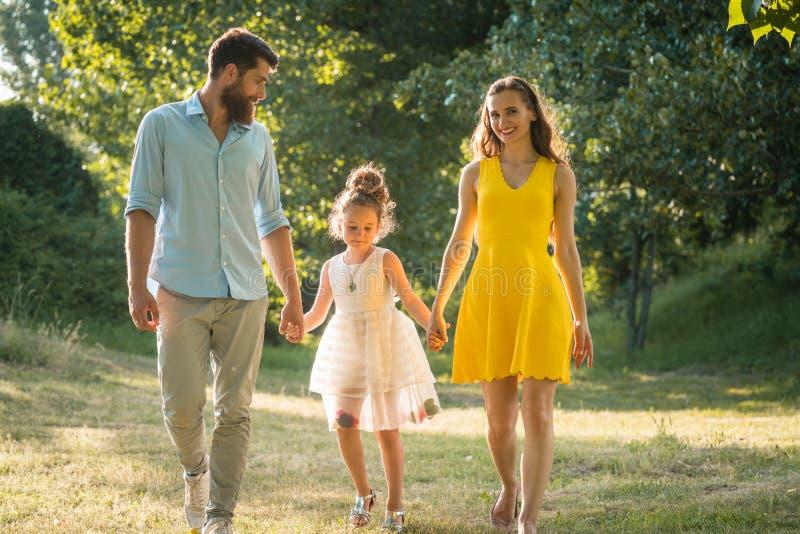 Preoccuparsi parents tenersi per mano della figlia mentre cammina insieme fotografia stock libera da diritti