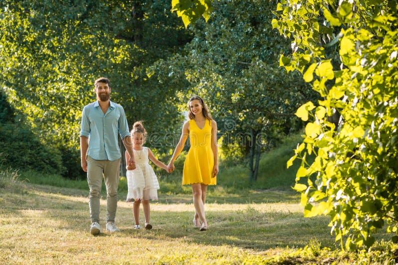Preoccuparsi parents tenersi per mano della figlia mentre cammina insieme nel parco immagini stock