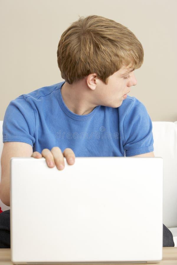 Preoccupato osservando ragazzo che per mezzo del computer portatile fotografia stock