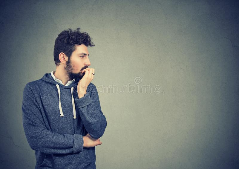 Preoccupied anxious man biting his fingernails royalty free stock images