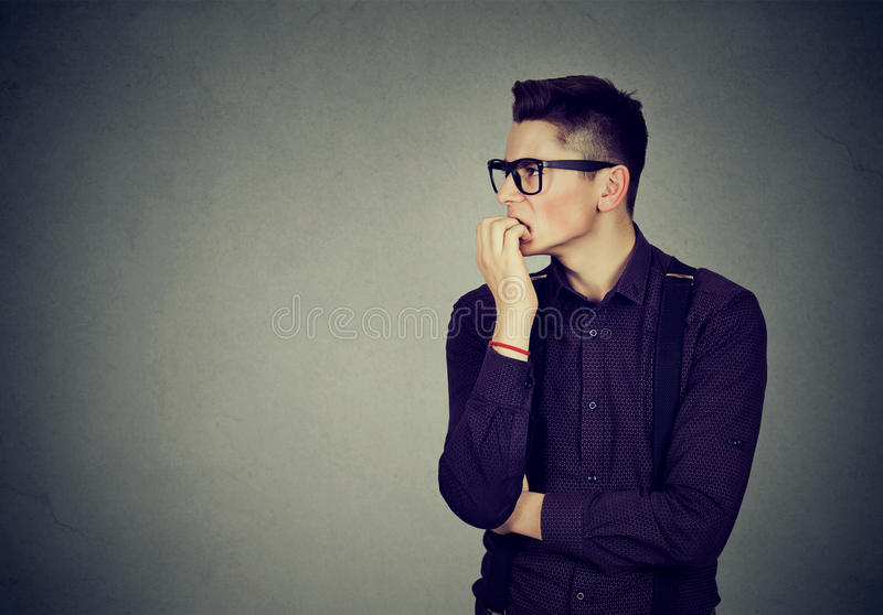 Preoccupied anxious man biting his fingernails stock images