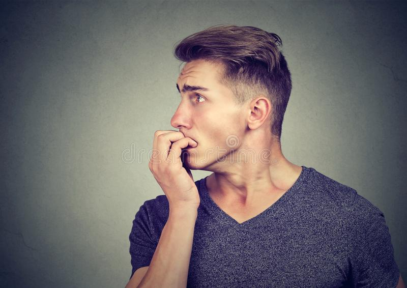 Preoccupied anxious young man biting his fingernails looking to the side. Preoccupied anxious man biting his fingernails looking to the side stock photos